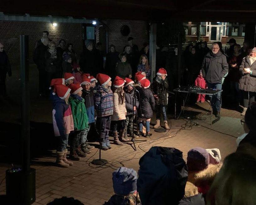 Kinder singen im Advent, mit Weihnachts-Mützen