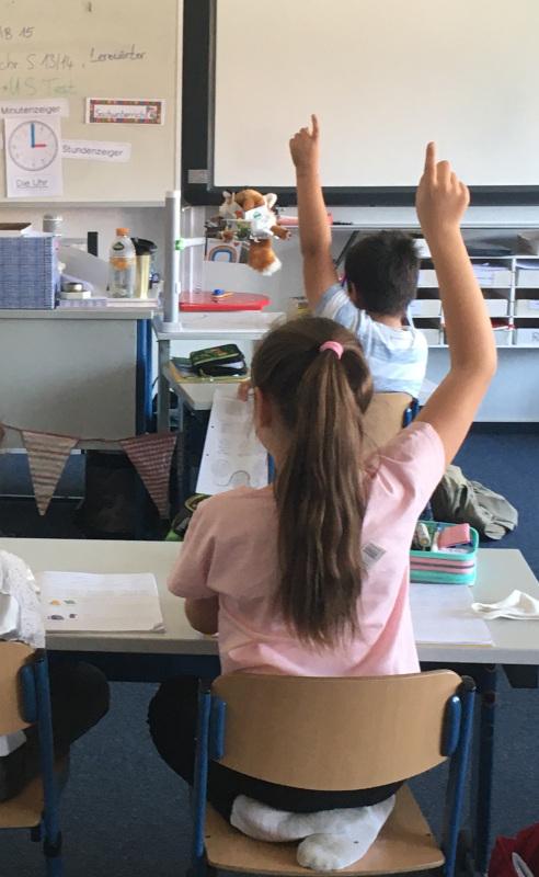 Kinder melden sich im Unterricht