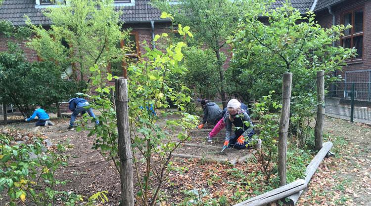 Kinder machen Gartenarbeit an der Schule